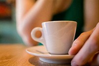 Mid section view of a woman holding a cup of coffee
