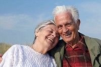 Head and shoulder photograph of elderly caucasian couple laughing and leaning to eachother while the senior man looking into the camera with blue sky,...