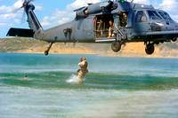 Staff Sgt  Kevin Myerscough enters the water after jumping from an HH-60 Pave Hawk helicopter, while Master Sgt  Michael Atkins gives the safe thumbs-...