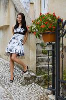 Happy young woman standing next to stylish traditional house entrance