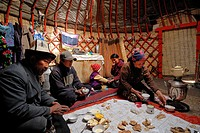 Kyrgyzstan, At Bashe High mountain pasture, Kirghiz sherperd and his family eating in his yurt