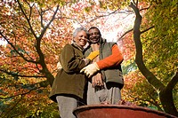 Senior African couple doing yard work in autumn