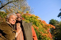Senior African couple hugging outdoors in autumn