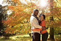 African couple hugging in park in autumn