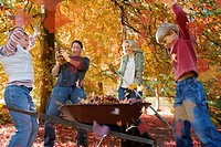 Family doing yard work and playing with autumn leaves
