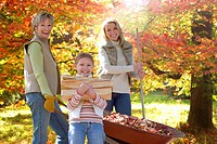 Three generation family doing yard work in autumn
