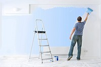 Man painting wall with paint roller near ladder