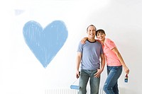 Couple smiling next to heart painted on wall