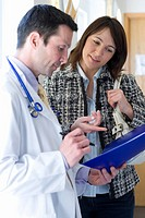 Doctor reviewing medical chart with female patient
