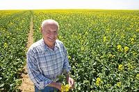 Smiling farmer standing in sunny rape seed field