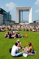 Lunch on the grass and Grande Arche, buildings of the business sector Paris La Defense, Paris, France
