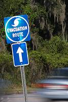 car whizzes by hurricane evacuation sign