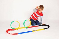 boy playing with racing car on floor, white background, Studio, Switzerland