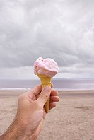 Male hand holding ice cream cone at beach on cloudy day