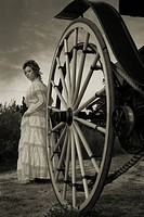 A model wearing a victorian dress near a cart wheel