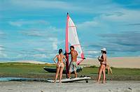Jericoacoara (Ceara, Brazil): a guy teaching windsurfing to two tourists by the beach