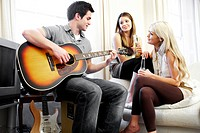 Three friends relaxing, playing guitar