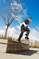 Male skateboarder riding edge along concrete curb