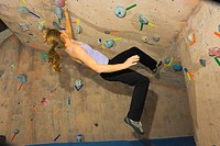 Woman climbing at rock gym