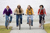 Four teenage girls on bikes laughing & having fun together Alaska USA