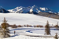 Woman running on winter snow covered road outside Telluride San Juan National Forest Colorado USA