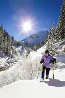 30_something worman snowshoeing along creek in San Juan Mountains Colorado Winter USA
