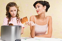 Woman giving her daughter a piece of burnt toast