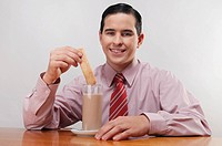 Businessman dipping a wafer into milk