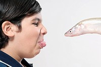 Boy facing a fish and making a disgust face