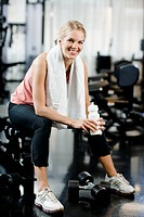 A woman with a water bottle at a gym Sweden.