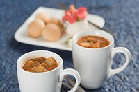 Two cups of tomato soup with bread cubes