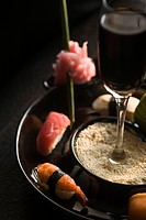 Close_up of sushi with a glass of wine in a plate
