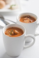 Close_up of two cups of tomato soup with bread cubes
