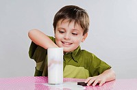 Close_up of a boy dunking cookies into milk