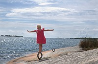 A girl skipping about on rocks Sweden.