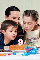 Boy and a girl blowing out birthday candles with their father