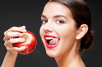 Woman eating a red apple and licking lips