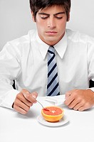 Close_up of a businessman eating a grapefruit with a spoon