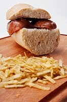 Close_up of a sausage sandwich and chips