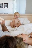 Young parents lying with baby 12_24 months in bed, baby sitting