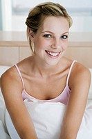 Young woman sitting on bed, smiling, portrait