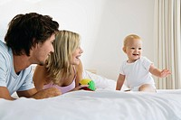 Young parents on bed with baby 6_12 months and toy, baby sitting up