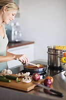 Young woman in modern kitchen, cooking pasta sauce, smiling (thumbnail)