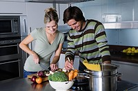 Young couple in modern kitchen, cooking pasta together, smiling