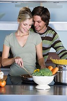 Young couple in modern kitchen, cooking together, hugging, smiling