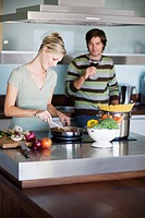Young couple in modern kitchen, cooking, drinking red wine