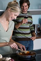 Young couple in modern kitchen, cooking together, smiling, drinking red wine