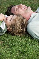 Father and son 4-7 lying on grass, looking up, laughing (thumbnail)