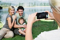 Girl photographing family outdoors, family posing for picture (thumbnail)