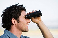 Man standing outdoors using binoculars, close_up